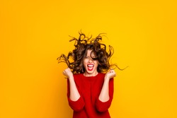 Photo of cheerful ecstatic funny hilarious victorious girlfriend rejoicing with wind blowing at her face isolated over yellow vivid color background