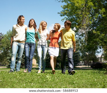 Photo of cheerful friends walking down green grass in park and chatting