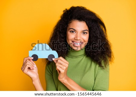 Photo of cheerful fun positive cute pretty nice girlfriend adverting you auto services her company provides holding paper car with hands isolated vivid color background