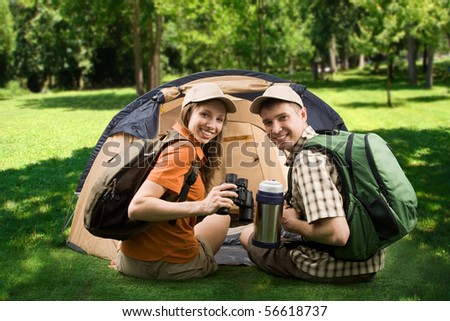 Photo of cheerful girl and guy sitting on green grass by tent and looking at camera with smiles