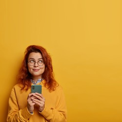 Photo of cheerful glad millennial girl with ginger hair uses mobile phone for sending text messages, thinks on message content for lover, wears yellow sweatshirt. Pleasant emotions, technology concept