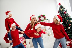 Photo of cheerful glad positive careless family members playing together having good relationship celebrating newyear at home in red jumpers