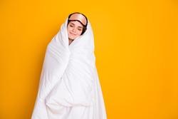 Photo of cheerful lady satisfied enjoy morning hug warm blanket eyes closed joyful facial expression wear mask white plaid pajama pants isolated yellow color background