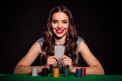 Photo of cheerful lady sit casino table hold two cards shiny smile wear glossy dress isolated black color background