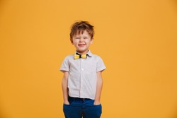 Photo of cheerful little boy child standing isolated over yellow background. Looking camera.