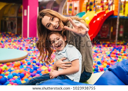 Photo of cheerful little child have fun with his mother in entertainment game center looking camera showing peace gesture.