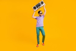 Photo of cheerful positive clubber guy hold boom box dance wear violet t-shirt isolated yellow color background