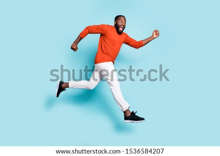 Photo of cheerful positive excited crazy running jumping black man wearing sneakers white trousers pants aspiring for sales isolated vivid blue color background