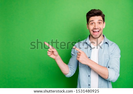 Photo of cheerful positive handsome man pointing at empty space expressing ecstatic emotions on face with bristle isolated over green vivid color background