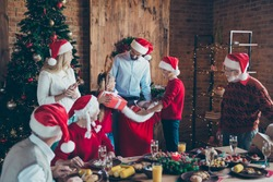 Photo of cheerful positive large family with father gifting presents to brother and sister small smiling toothily several generations meeting in santa caps