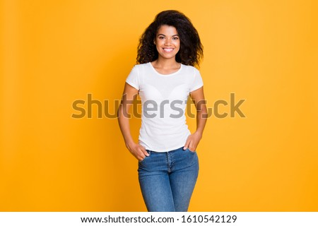 Photo of cheerful positive nice cute girlfriend with hands in pocket standing confidently in white t-shirt isolated over vivid color background in jeans denim