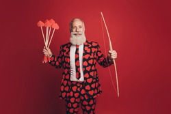 Photo of cheerful retired cherub archer hold bow arrow look camera wear heart print tux isolated red background