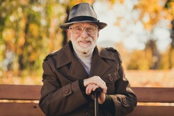 Photo of cheerful retired old grey haired grandpa street central park sit bench positive emotions enjoy sunny day weather hold walking cane stick wear autumn glasses jacket hat outside