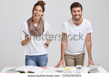 Photo of cheerful woman and man designers dressed in fashionable clothes, stand near white desk, study literature, make project work on tablet, connected to wireless internet. People and profession