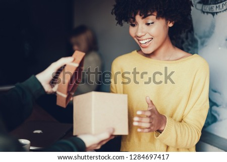 Photo of cheerful young woman with smile looking in present box. Man opening gift to surprising her lady #1284697417