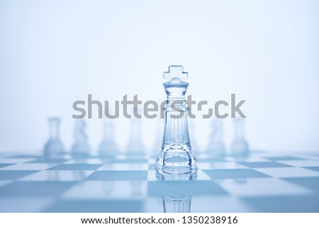 Photo of chess king standing in checkerboard front of the same colour set in bright background. #1350238916