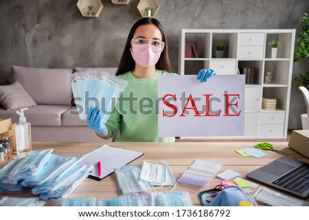 Photo of Photo of chinese business lady make picture internet blog workplace hold hands sale proposition placard order facial flu cold masks packs free delivery home office quarantine indoors