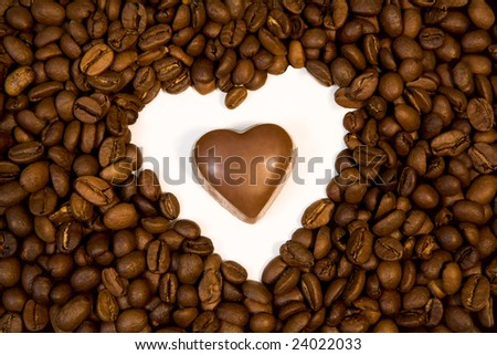Photo of chocolate candy inside shape of heart made up of coffee beans