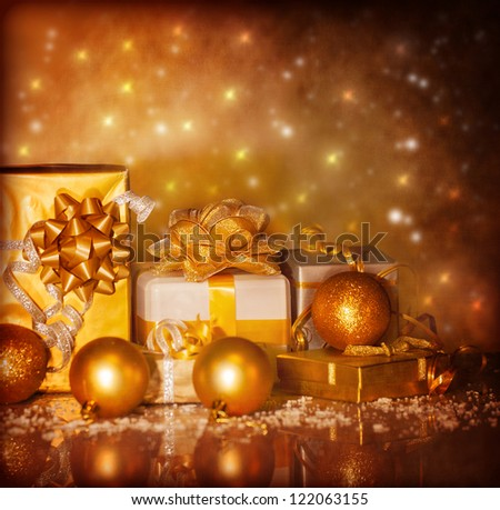 Photo of Christmas present boxes on grunge shiny background, New Year gifts wrapping in beautiful golden paper with ribbon bow, Xmas surprise, luxury festive decorations, Christmastime ornament