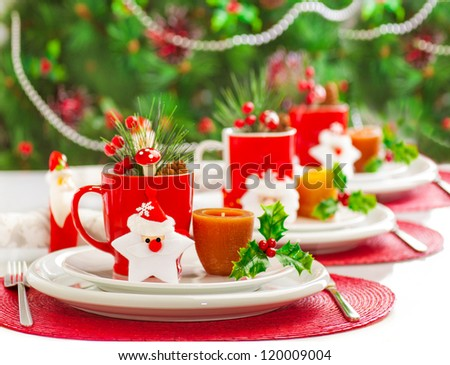 Photo of Christmas table decoration, festive dinnerware with candles and red cups for tea in decorated dinner room, luxury utensil, New Year party, Christmastime table setting, xmas decor