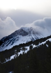 Photo of clouds engulfing a mountain in the the Canadian rockys.