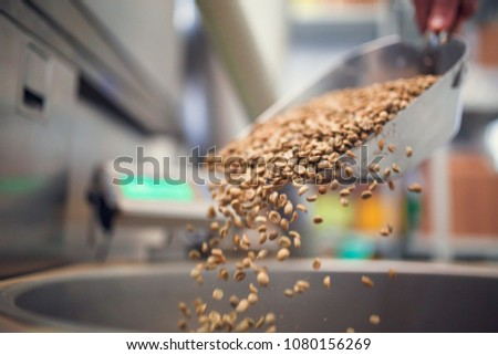 Photo of coffee beans poured from iron scoop