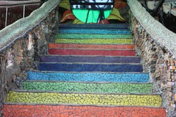 photo of colorful, fabulous staircase. beautiful scenery.patterned railing.the stairs are made of colored tiles.the staircase is decorated with pebbles and shells.