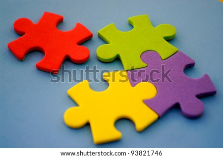 Photo of colorful puzzles with red piece separated and focus on red.