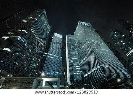 Photo of commercial office buildings exterior. Night view at bottom skyscrapers.