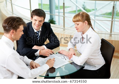Photo of company of successful people discussing new project in office