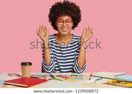 Photo of concentrated relaxed dark skinned young woman makes okay gesture with both hands, meditates at workplace, feels calm and relaxed, dressed in striped clothes, isolated on pink, draws picture