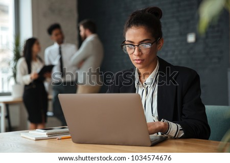 Photo of concentrated young african business woman sitting indoors using laptop computer. Looking aside.