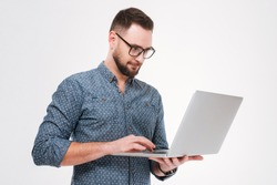 Photo of concentrated young bearded man wearing glasses dressed in shirt using laptop isolated over white background.