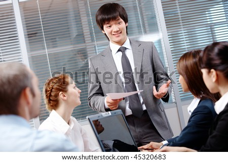 Photo of confident businessman making report to partners at conference