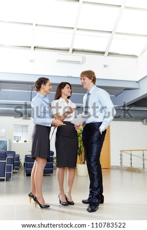 Photo of confident businesspeople standing in the modern office and discussing work