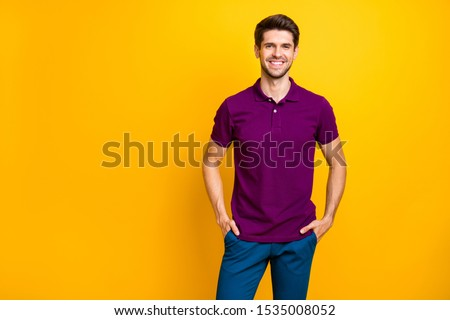 Photo of confident cheerful reliable business person holding his hands in pockets smiling toothily beaming looking successful isolated over yellow vivid color background