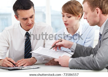 Photo of confident employees discussing papers at meeting