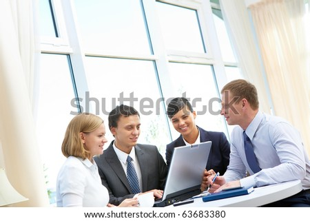Photo of confident employees working round table in office