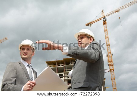 Photo of confident engineer showing something to his partner at building site