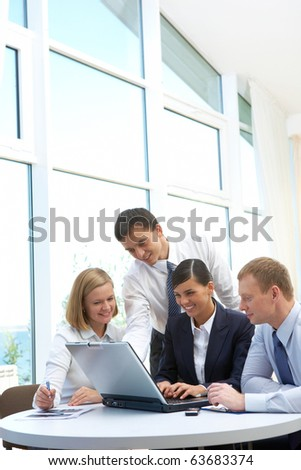 Photo of confident partners planning work at meeting in office
