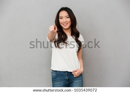 Photo of content woman 20s in casual t-shirt and jeans pointing finger on camera with smile isolated over gray background #1035439072