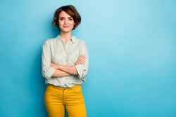 Photo of cool attractive business lady short hairstyle friendly smiling responsible person arms crossed wear casual green shirt yellow pants isolated blue color background