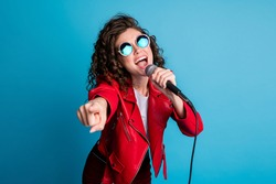 Photo of crazy carefree lady open mouth sing hold mic direct finger on you wear round sunglass isolated on blue color background