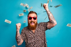 Photo of crazy handsome guy luxury rich person dollars fall from sky lottery cashback open mouth win big money raise fists wear leopard shirt sun specs isolated blue background