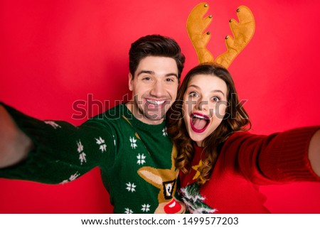 Photo of crazy lady and guy at x-mas costume party making selfies wear knitted jumpers with ornament isolated red color background