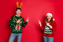Photo of crazy lady and guy directing fingers empty space on x-mas sale wear funky ugly ornament pullovers isolated red color background