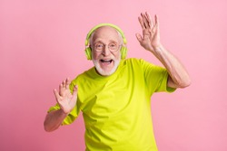 Photo of crazy optimistic old man listen music dance arms wear headphones spectacles lime color clothes isolated on pink background