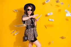 Photo of crazy positive girl spend waste hundred dollars credit bank earnings air fly money isolated over bright shine color background wear headwear skirt sunglass