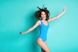 Photo of crazy tourist girl enjoy ocean breeze wind blow haircut have thin shape, wear blue bodysuit isolated over turquoise color background
