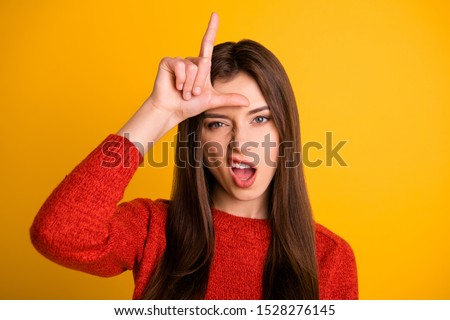 Photo of cruel rude bad school youngser showing you lose sign grimacing arrogant facial expression isolated over yellow vibrant color background